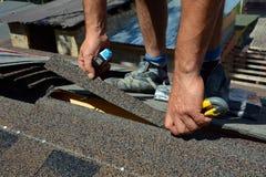 Reparación de una techumbre de tablas El fieltro o el betún de la techumbre del corte del Roofer durante la impermeabilización tr Foto de archivo libre de regalías