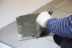 Reparación - decoración interior Colocación de las baldosas cerámicas del piso El solador de las manos del ` s de los hombres en  foto de archivo libre de regalías