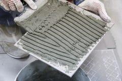 Reparación - decoración interior Colocación de las baldosas cerámicas del piso El solador de las manos del ` s de los hombres en  imágenes de archivo libres de regalías