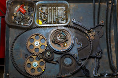 Reparación del coche con la correa y los engranajes en tabla del grunge Foto de archivo
