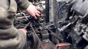 Reparación del coche El mecánico de la mano tuerce el aceite del dren tapa en el coche almacen de metraje de vídeo