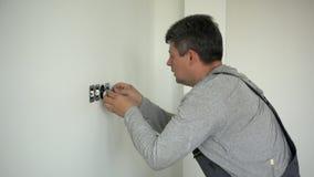 Reparación del hombre del electricista un zócalo eléctrico del mercado en el apartamento almacen de video