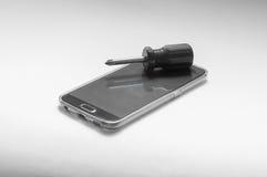 Reparación del Smart-teléfono con un destornillador Imagen de archivo libre de regalías