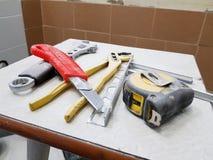 Reparación - edificio con las herramientas llave, cuchillo, cuchillo del hierro, llave ajustable y cinta métrica en un taburete imagen de archivo
