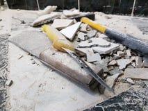 Reparación - el edificio con las herramientas martilla, almádena, cuchilla y un cuchillo con los cascos de la teja imagen de archivo