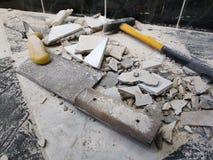 Reparación - el edificio con las herramientas martilla, almádena, cuchilla y un cuchillo con los cascos de la teja imagenes de archivo
