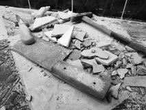 Reparación - el edificio con las herramientas martilla, almádena, cuchilla y un cuchillo con los cascos de la teja fotos de archivo