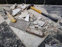Reparación - el edificio con las herramientas martilla, almádena, cuchilla y un cuchillo con los cascos de la teja fotografía de archivo libre de regalías