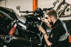 Reparaciones de trabajo del destornillador y de la motocicleta del mecánico profesional imágenes de archivo libres de regalías