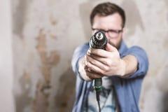 Reparaciones en el apartamento Un hombre frustrado sostiene un dri eléctrico fotografía de archivo libre de regalías