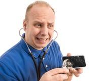 Reparador ansioso Checks Broken Smartphone con el estetoscopio Imágenes de archivo libres de regalías
