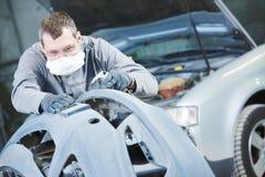 Reparador auto que muele el capo autobody Fotografía de archivo libre de regalías
