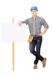 Reparador de sexo masculino que se inclina en una bandera en blanco Imágenes de archivo libres de regalías