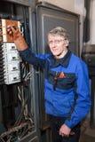 Reparador del electricista en el panel industrial de alto voltaje cercano derecho uniforme del azul Fotografía de archivo