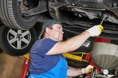 Reparador do mecânico de automóvel que fixa um carro na estação do serviço Imagens de Stock Royalty Free
