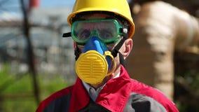 Reparador en casco, gafas y respirador en el área industrial metrajes