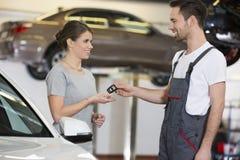 Reparador feliz que dá a chave do carro à mulher na oficina imagens de stock royalty free