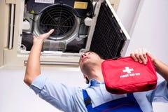 Reparador joven que repara la unidad de aire acondicionado del techo fotografía de archivo