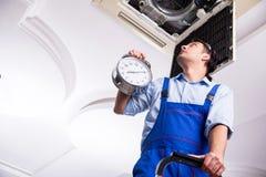 Reparador joven que repara la unidad de aire acondicionado del techo imagenes de archivo