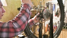 Reparador masculino novo da bicicleta com uma chave especializada em um suporte na oficina, apertando os raios da roda filme