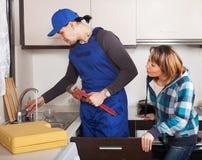 Reparador ordinario que trabaja en la cocina Imágenes de archivo libres de regalías