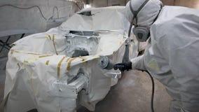 Reparador profesional que pinta un coche en un garaje que lleva la ropa y la máscara protectoras almacen de video