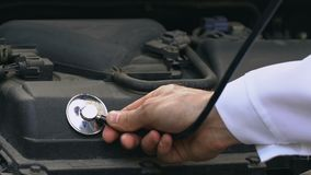 Reparador que comprueba el motor del coche con el estetoscopio, inspección del vehículo, transporte metrajes