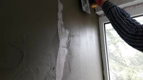 Reparador que enyesa la pared con la espátula metrajes