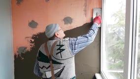 Reparador que enyesa la pared con la espátula almacen de video