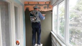 Reparador que enyesa la pared con la espátula almacen de metraje de vídeo