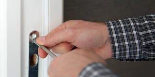 Reparador que fixa uma fechadura da porta Imagens de Stock