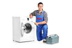 Reparador que presenta al lado de una lavadora Imágenes de archivo libres de regalías