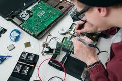 Reparador que solda componentes eletrônicos no processador central imagens de stock royalty free