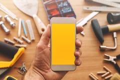 Reparador que sostiene el teléfono elegante con la pantalla en blanco a disposición fotografía de archivo