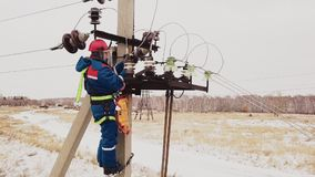 Reparador que trabaja en la línea eléctrica con los alambres del voltaje en la estación almacen de metraje de vídeo