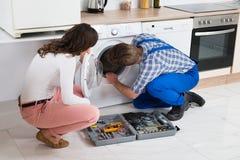 Reparador Repairing Washer In Front Of Woman Fotografía de archivo libre de regalías