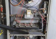Reparador Vacuuming Inside Of un horno de gas Fotografía de archivo