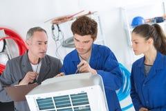 Reparadores del aire acondicionado que discuten problema con la unidad del compresor imagen de archivo