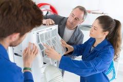 Reparadores del aire acondicionado que discuten problema con la unidad del compresor fotos de archivo
