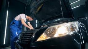 Reparando trabajos están siendo sostenidos en un automóvil por un técnico almacen de video