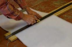 Reparatie, de bouw en huisconcept - sluit omhoog van mannelijke handen die behang meten stock fotografie