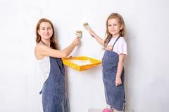 Reparatie in de flat De gelukkige familiemoeder en weinig dochter in blauwe schorten schilderen de muur met witte verf royalty-vrije stock foto's