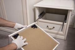 Reparatie en installatie van meubilair in de ruimte De mannelijke arbeider ` s dient witte handschoenen in royalty-vrije stock afbeelding