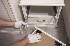 Reparatie en installatie van meubilair in de ruimte De mannelijke arbeider ` s dient witte handschoenen in stock afbeelding