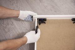 Reparatie en installatie van meubilair in de ruimte De mannelijke arbeider ` s dient witte handschoenen in stock foto