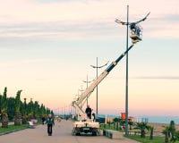 Reparatie en onderhoud van straatlantaarns in de straat van het stadspark bij zonsondergang in avond - de kraan hief elektricien  Royalty-vrije Stock Foto's