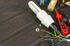 Reparatie gebroken lichten Energie - besparings gloeilamp op een donkere achtergrond Verkoop van gloeilampen Reclame op verlichti Stock Foto's