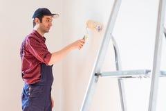 Reparatie, het vernieuwen en huisconcept met mens het schilderen muur thuis stock afbeeldingen