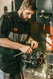 Reparatie van de motorfiets de mechanische motor bij benzinestation stock afbeeldingen