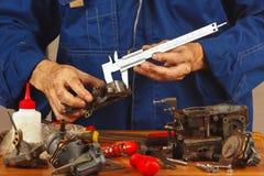 Reparatie van delen van automobielmotor in workshop stock fotografie